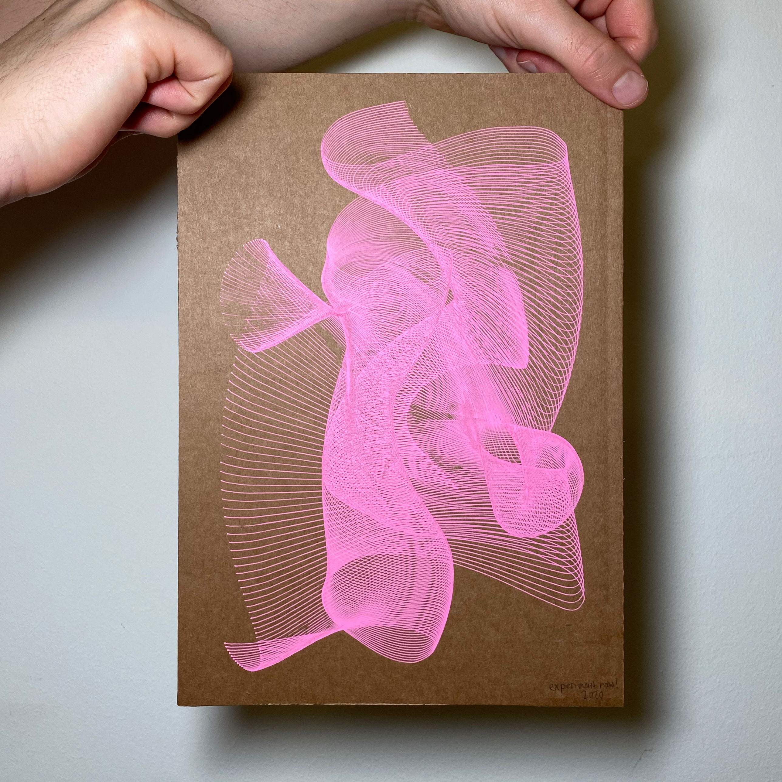 Two hands are holding a used cardboard in the size of A4 with neon pink abstract lines on it.