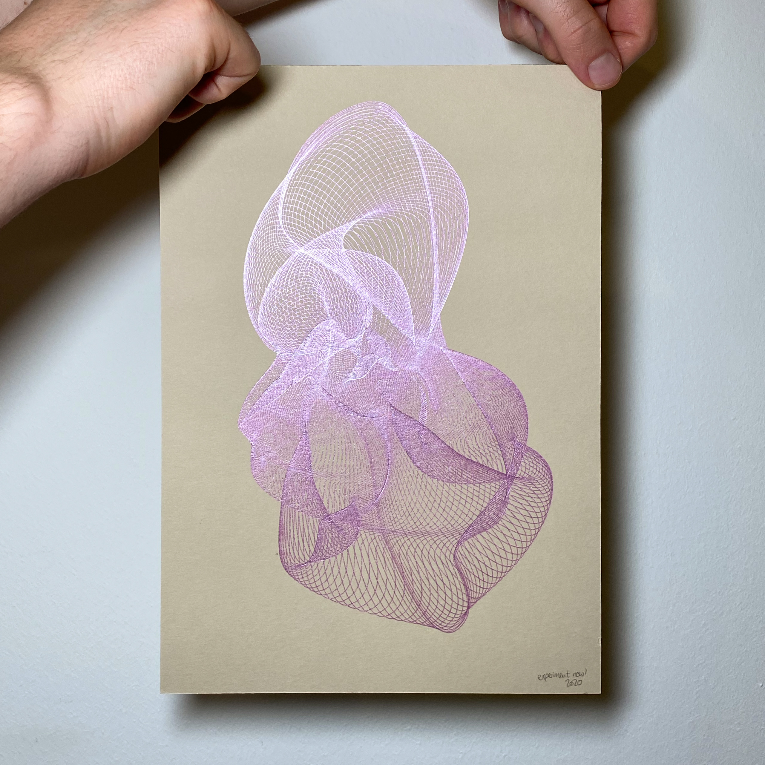 Two hands are holding a beige page (size: A4) with generative art in metallic pink on it.